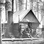 Officers quarters, showing common winter lodgings of log walls and fireplace with tent for roof.